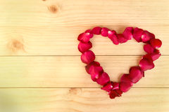 Heart shape made out of rose petals on wood background, Valentin Stock Photos