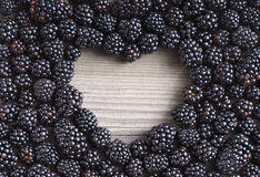 Heart shape made of premium Blackberries on wooden background. Royalty Free Stock Image
