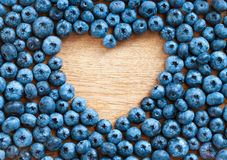 Heart shape made of premium Blueberries on wooden background. royalty free stock photo