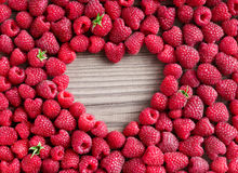 Heart shape made of premium raspberries on wooden background. Stock Image