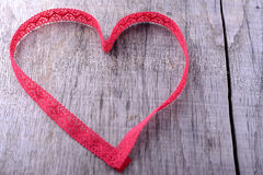 Heart shape made of red lace ribbon on a wooden Royalty Free Stock Photos