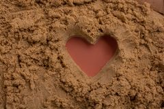 Heart shape made on the sand background. In view stock image