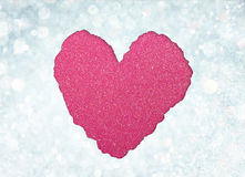 Heart shape made from torn paper over glitter boke soft lights. Royalty Free Stock Images