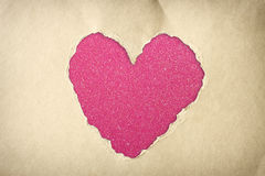 Heart shape made from torn paper over glitter boke soft lights. Royalty Free Stock Photo