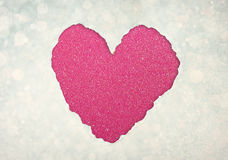 Heart shape made from torn paper over glitter boke soft lights. Stock Images