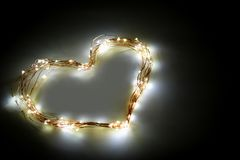 Heart shape made from twinkle lights on black background. Card design and decoration royalty free stock image