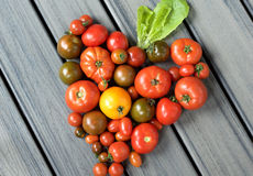 Heart shape made from a variety of tomatoes. Variety of differnt colored tomatoes arranged togehter to create a heart shape royalty free stock photos