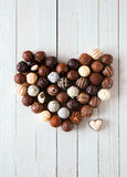 Heart shape made with various chocolate truffles. Heart shape made with various types of chocolate truffles over a white wooden table royalty free stock photos