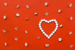 Heart shape made of white pills with white flowers pattern on or Stock Photo