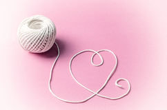 HEART SHAPE MADE OF WHITE THREAD. Image of a white thread forming heart shape with pink background. Using Retro effect Royalty Free Stock Images