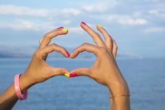 Heart shape made of woman hands against sea and sky Stock Images