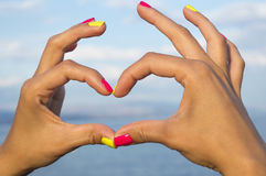 Heart shape made of woman hands against sea and sky Royalty Free Stock Photography