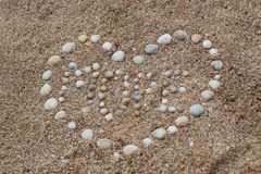 Heart shape maked of sea shells on sand royalty free stock photo