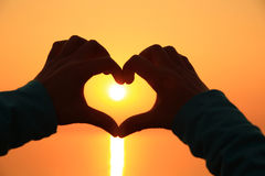 Heart shape making of hands against bright sea sunset Royalty Free Stock Photography