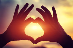 Heart shape making of hands against bright sea sunset Stock Photo
