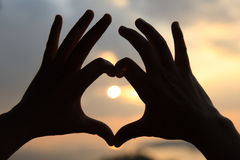 Heart shape making of hands against bright sea sunset Stock Image