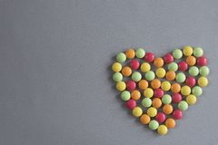 Heart shape from multi-colored tablets of dragees on a gray woven background. The figure of the heart, consisting of multicolored tablets of drags on a gray Stock Images