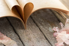 Heart shape from opened book pages on wood background. Royalty Free Stock Images