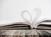Heart shape in opened notebook page, on wooden table Royalty Free Stock Photos