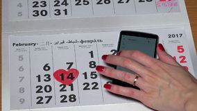 Heart shape painted on paper calendar and woman hand touching smart phone. VILNIUS, LITHUANIA - NOVEMBER 30, 2016: Heart shape painted on paper calendar on stock video