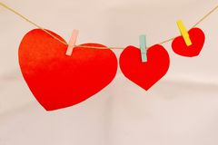 Heart shape papers hanging on cloth line with cloth pins. Close view Stock Photos