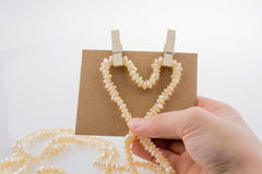 Heart shape of pearls in hand Stock Image