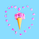 Heart shape of petals with ice cream cone with flowers over colorful blue Stock Photos
