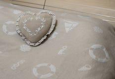 Heart shape pillow on the blanket Stock Photos