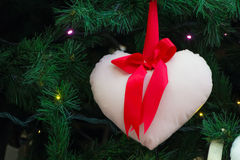 Heart shape pillow decorated on a christmas tree Stock Photo
