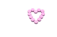 Heart shape of pink pills isolated on white background. Royalty Free Stock Image