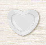 Heart shape plate on wodden table Royalty Free Stock Photography