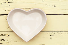 Heart shape plate. On wooden table Stock Image