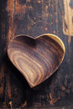 Heart shape plate on wooden table Royalty Free Stock Photo