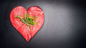 Heart shape raw meat with herbs on dark chalkboard background. Healthy lifestyle or organic food concept Stock Photos