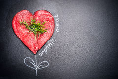 Heart shape raw meat with herbs with painted  Organic meat inscription around . Dark chalkboard background. Royalty Free Stock Photography