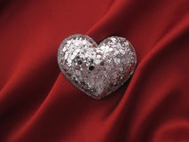 Heart shape on red. Silver heart shape on red silk background Stock Photos