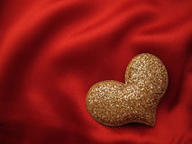 Heart shape on red. Gold heart shape on red silk background Royalty Free Stock Images