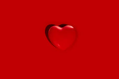 Heart shape on red. Red heart shape on plain red background Royalty Free Stock Images