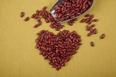 Heart shape of red kidney beans with scoop. On green cloth Royalty Free Stock Photos