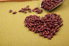 Heart shape of red kidney beans with scoop. On green cloth Stock Photos