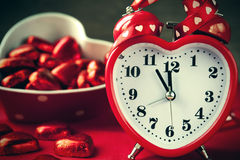 Heart shape red love clock and chocolated. Heart shape red love clock and chocolates on red background. Time for sweet love Stock Images
