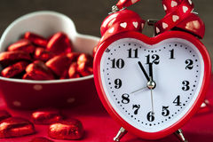 Heart shape red love clock and chocolates. On red background. Time for sweet  love Stock Image