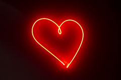 Heart shape red neon lights. Heart shape neon lights in a dark background Stock Images