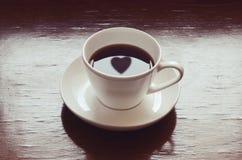Heart shape reflections on black coffee. Heart shape reflected on black coffee, sunlight through a window stock photography