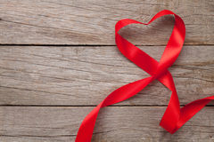 Heart shape ribbon over wood valentines day background Stock Photo