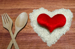 Heart shape of rice with red heart on valentine's day, Jasmine rice. Heart shape of rice with red heart on valentine's day, Jasmine rice in wooden spoon on Royalty Free Stock Photo