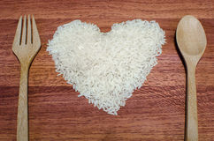 Heart shape of rice on valentine's day, Jasmine rice with wooden spoon. On wooden table (close-up shot), jasmine rice grain, uncooked rice Royalty Free Stock Photo