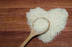 Heart shape of rice on valentine's day, Jasmine rice with wooden spoon. On wooden table (close-up shot), jasmine rice grain, uncooked rice Stock Images