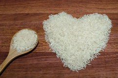 Heart shape of rice on valentine's day, Jasmine rice with wooden spoon. On wooden table (close-up shot), jasmine rice grain, uncooked rice Stock Image