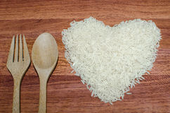 Heart shape of rice on valentine's day, Jasmine rice with wooden spoon. On wooden table (close-up shot), jasmine rice grain, uncooked rice Royalty Free Stock Photography